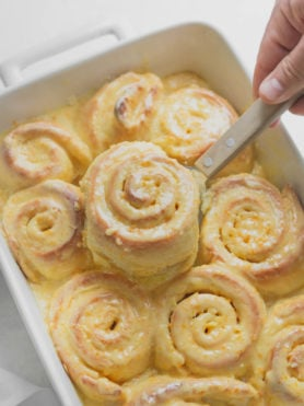 An orange roll being lifted from a pan of freshly baked orange rolls. The rolls are frosted with an orange glaze.