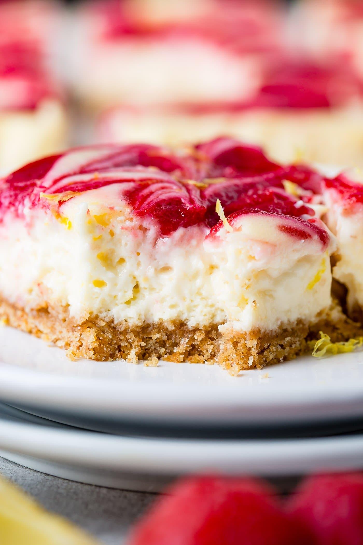 A close-up of a swirled raspberry lemon cheesecake bar. the top has raspberry sauce swirled in.
