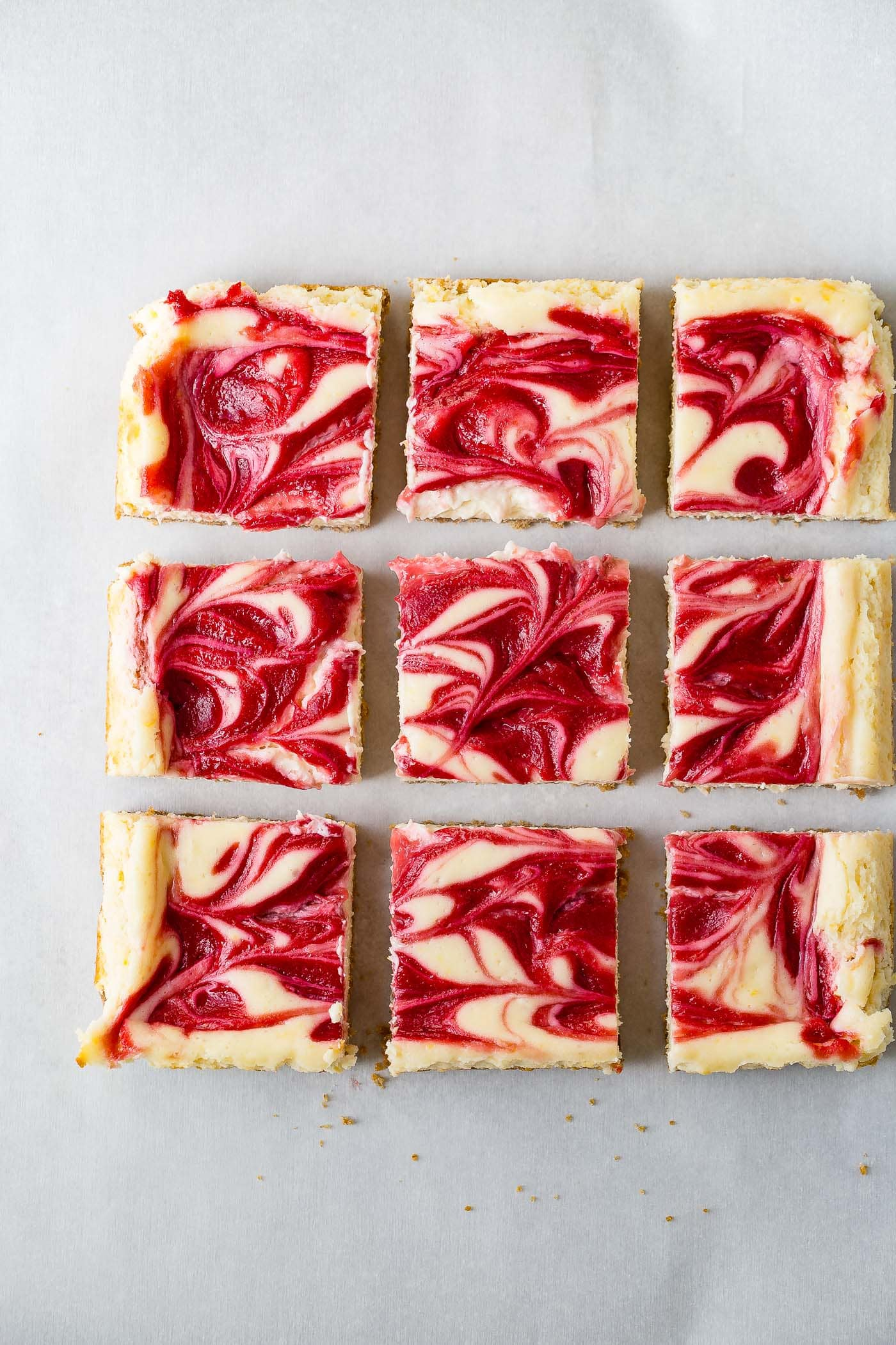 Nine cut squares of swirled raspberry lemon cheesecake bars. They have a golden crust and lemon cheesecake filling with raspberry sauce swirled on top.