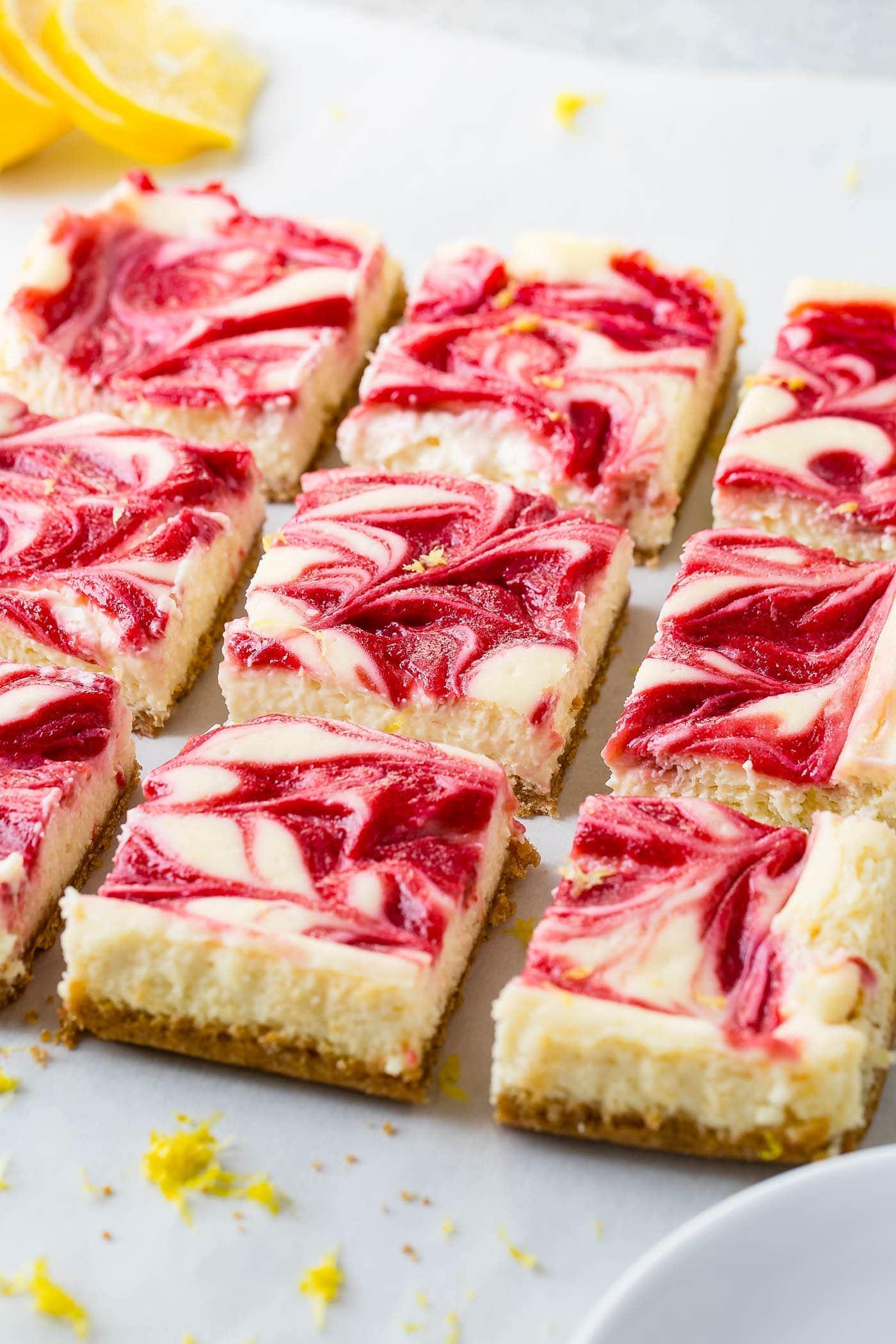 Nine cut squares of swirled raspberry lemon cheesecake bars. The light yellow lemon cheesecake has swirls of raspberry sauce on top.