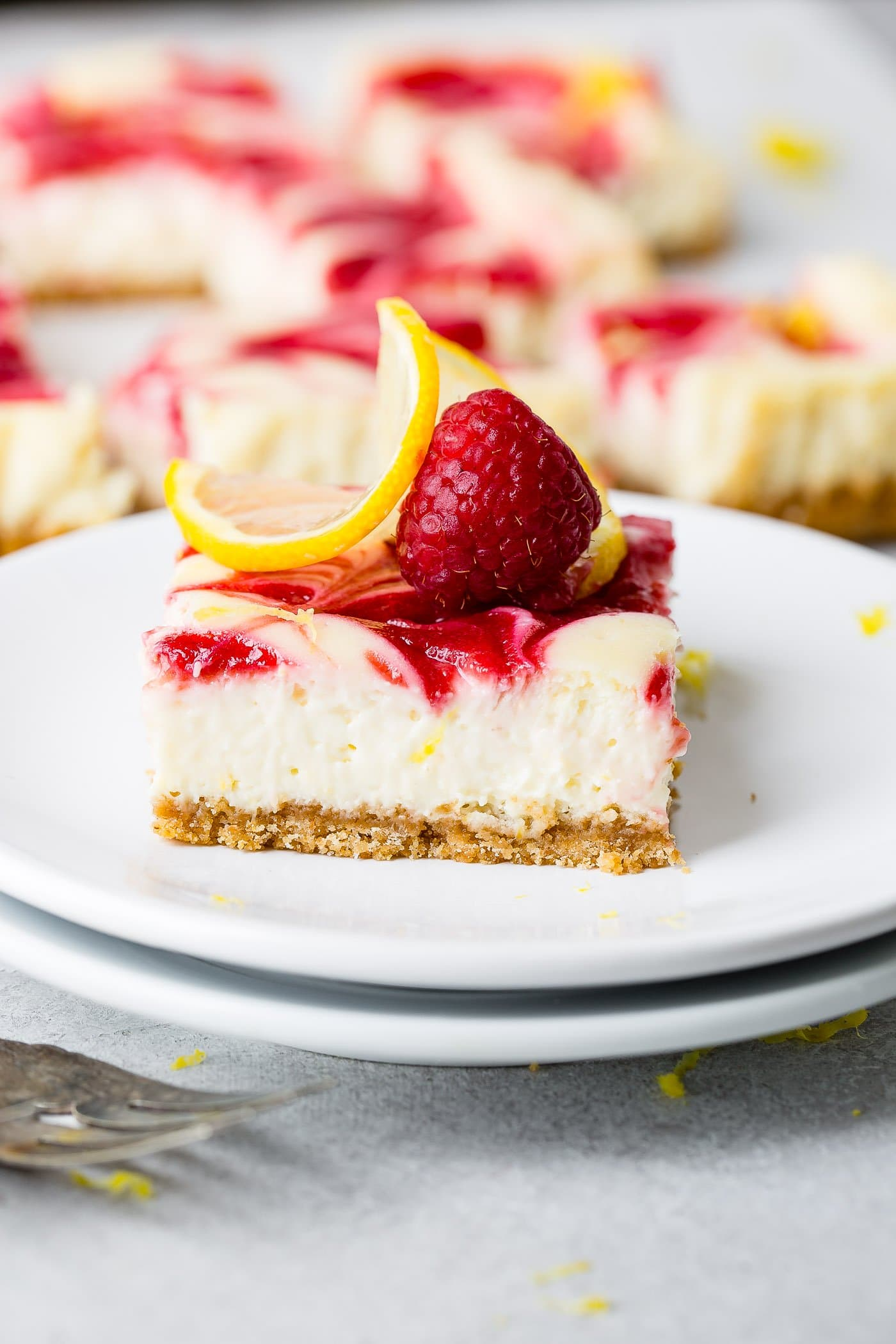A serving of swirled raspberry lemon cheesecake on a dessert plate. It is topped with a thin slice of lemon and a raspberry. There are other pieces of cheesecake in the background.