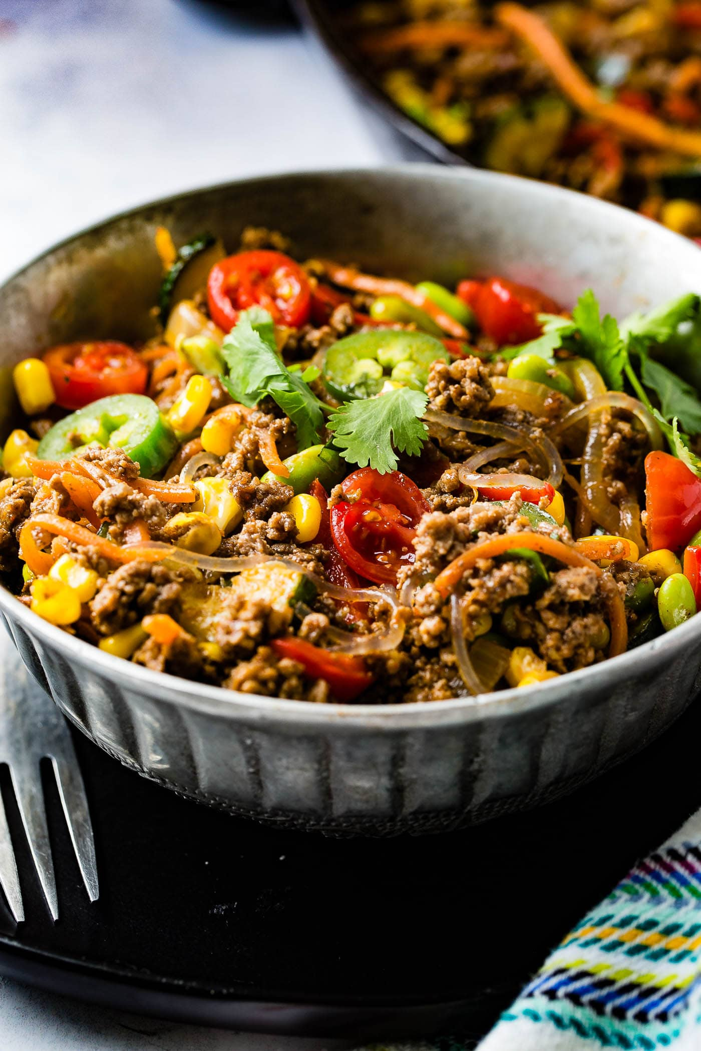 A bowl of taco pasta skillet. There are sliced tomatoes, sliced jalapenos, ground beef, zucchini, carrots, and fresh parsley.