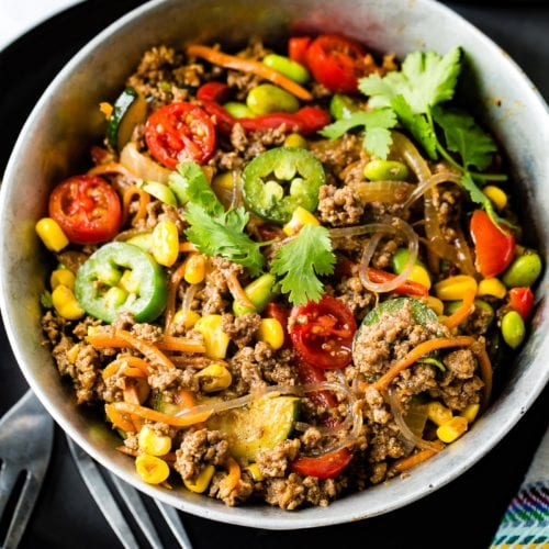 A bowl of taco stir-fry. There is ground beef, tomatoes, jalapenos, pasta, corn and zucchini. It is sprinkled with fresh parsley. Two forks are next to the bowl.