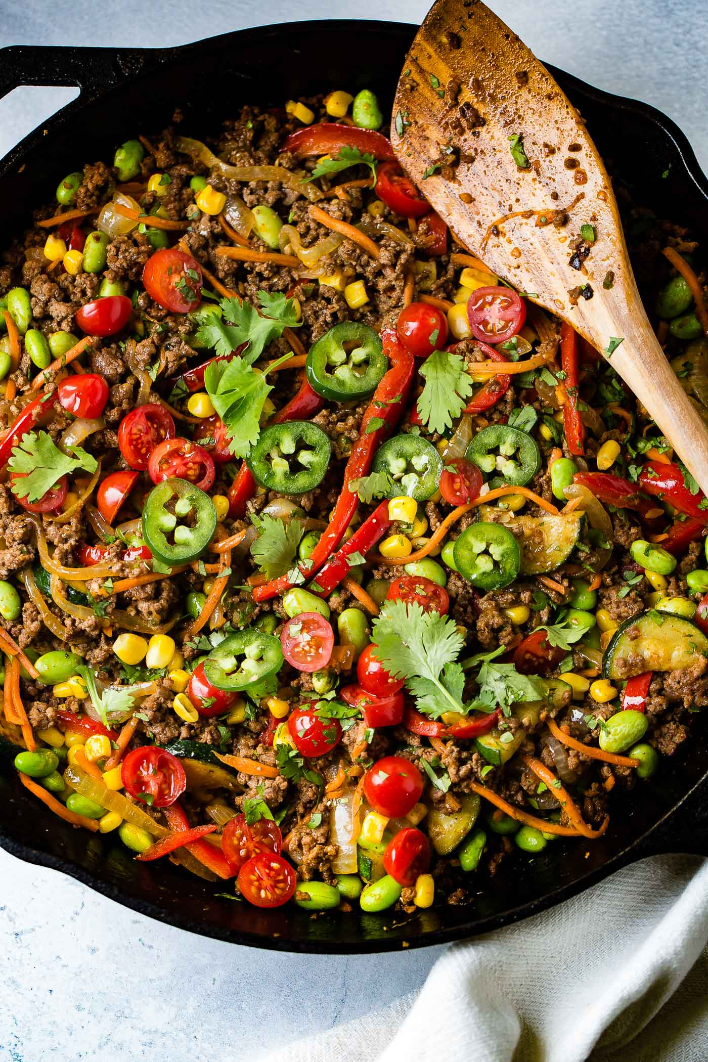 Taco skillet. There is a wooden spoon laying across the cast iron skillet. There are sliced tomatoes, sliced jalapeno, carrots, corn, pasta and ground beef.