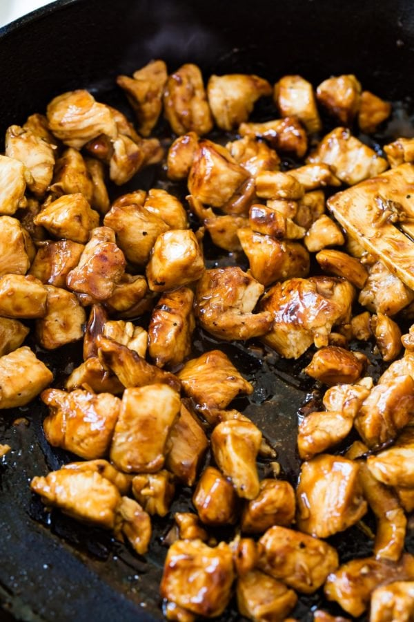 A photo of teriyaki chicken being cooked in a skillet.