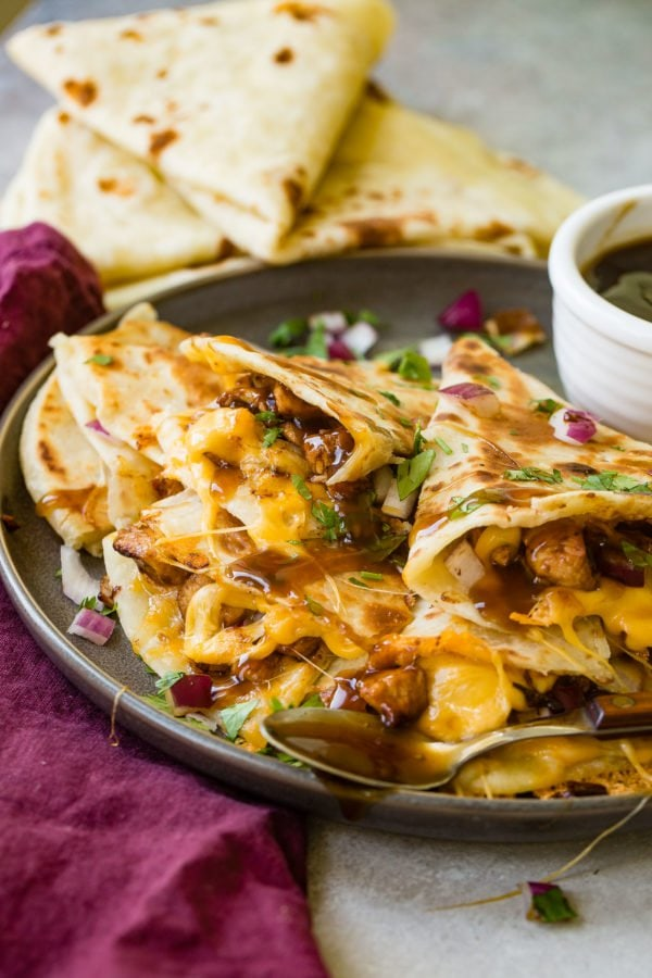 A photo of several slices of teriyaki chicken quesadilla garnished with minced red onion and chopped fresh cilantro.