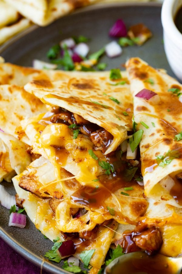 A photo of a slice of teriyaki chicken quesadilla garnished with minced red onion and chopped fresh cilantro.