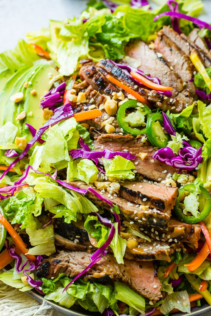 A grey plate full of mixed greens, veggies and thai peanut sauce marinated steak with a ginger dressing and sesame seeds
