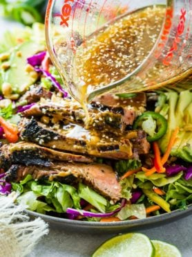 A grey plate full of mixed greens, veggies and thai peanut sauce marinated steak and a ginger dressing being poured over the top