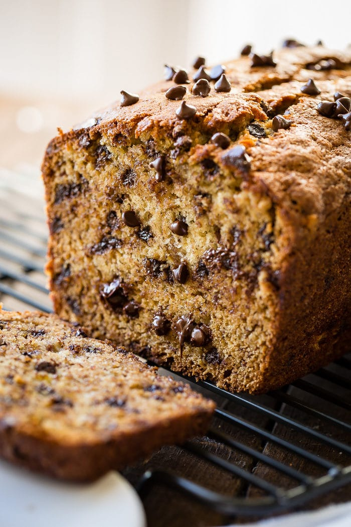 Chocolate chip banana bread sliced in half, cooling on a rack.