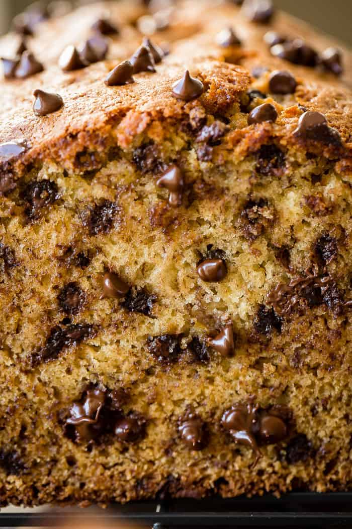 A close up shot of a moist loaf of chocolate chip banana bread on a cooling rack
