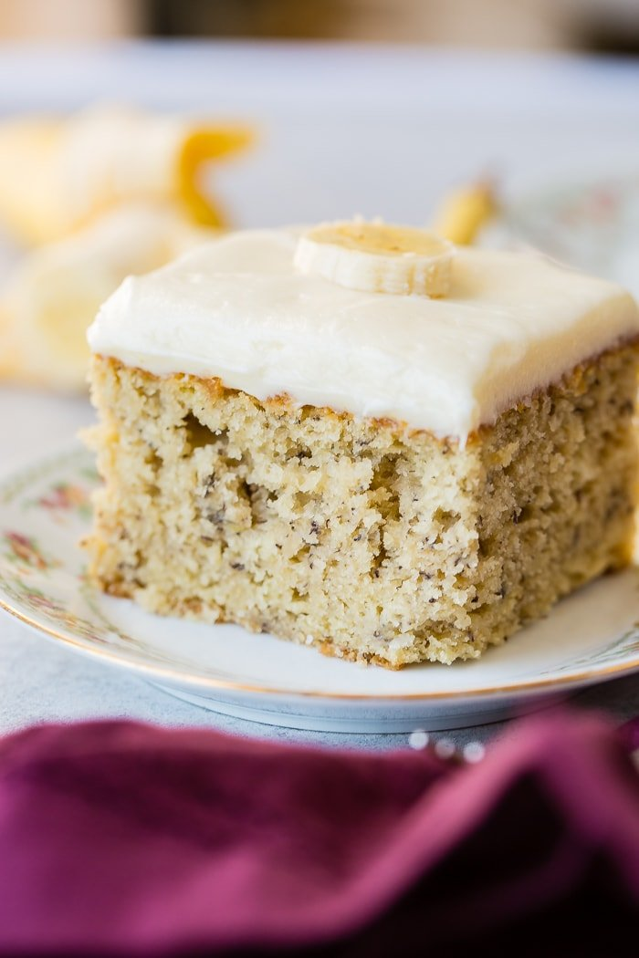 a slice of moist banana cake with cream cheese frosting