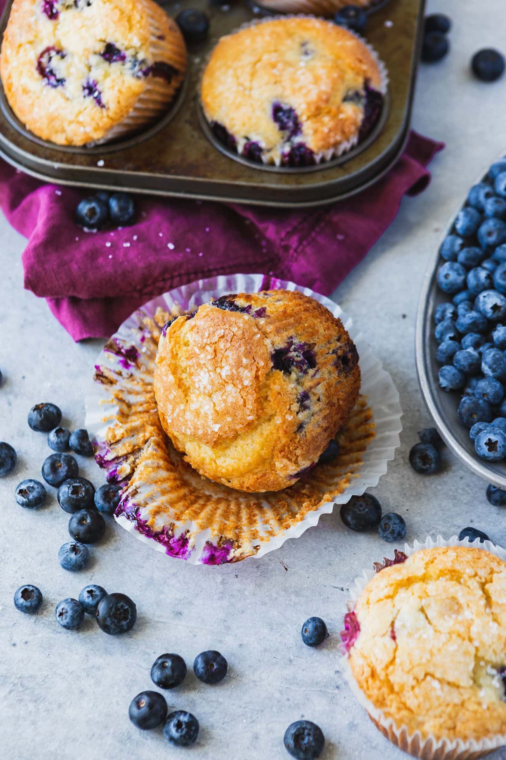 A blueberry muffin with parchment peeled down, there's blueberries appearing in muffins and blueberries on the table next to muffins, and there's a muffin tin with other muffins in the background.