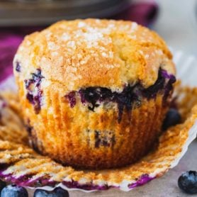 A blueberry muffin with the paper liner peeled back so you can see the golden brown muffin packed with blueberries.