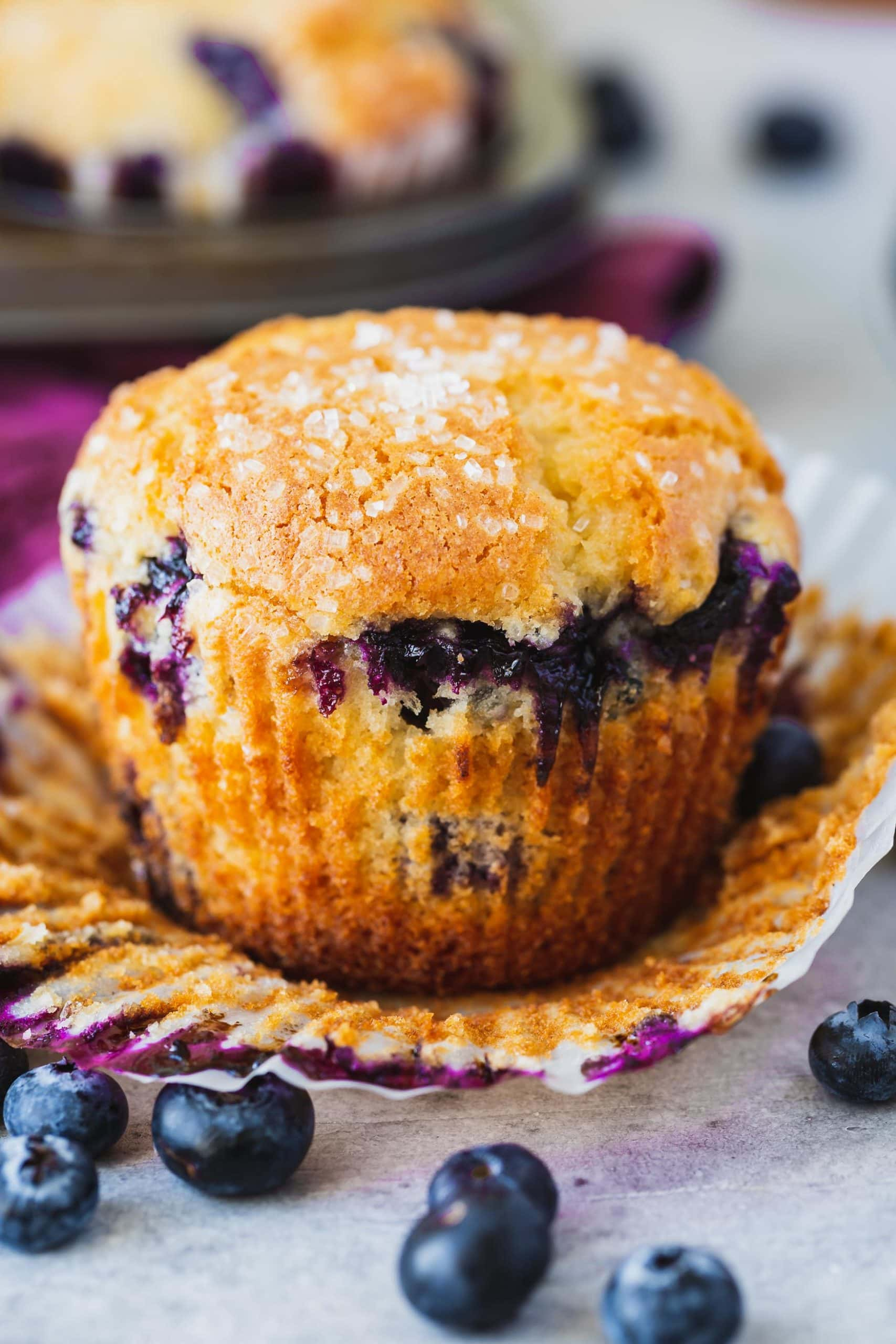 Raspberry cake with paper lining peeled back so you can see golden brown cakes filled with blueberries.
