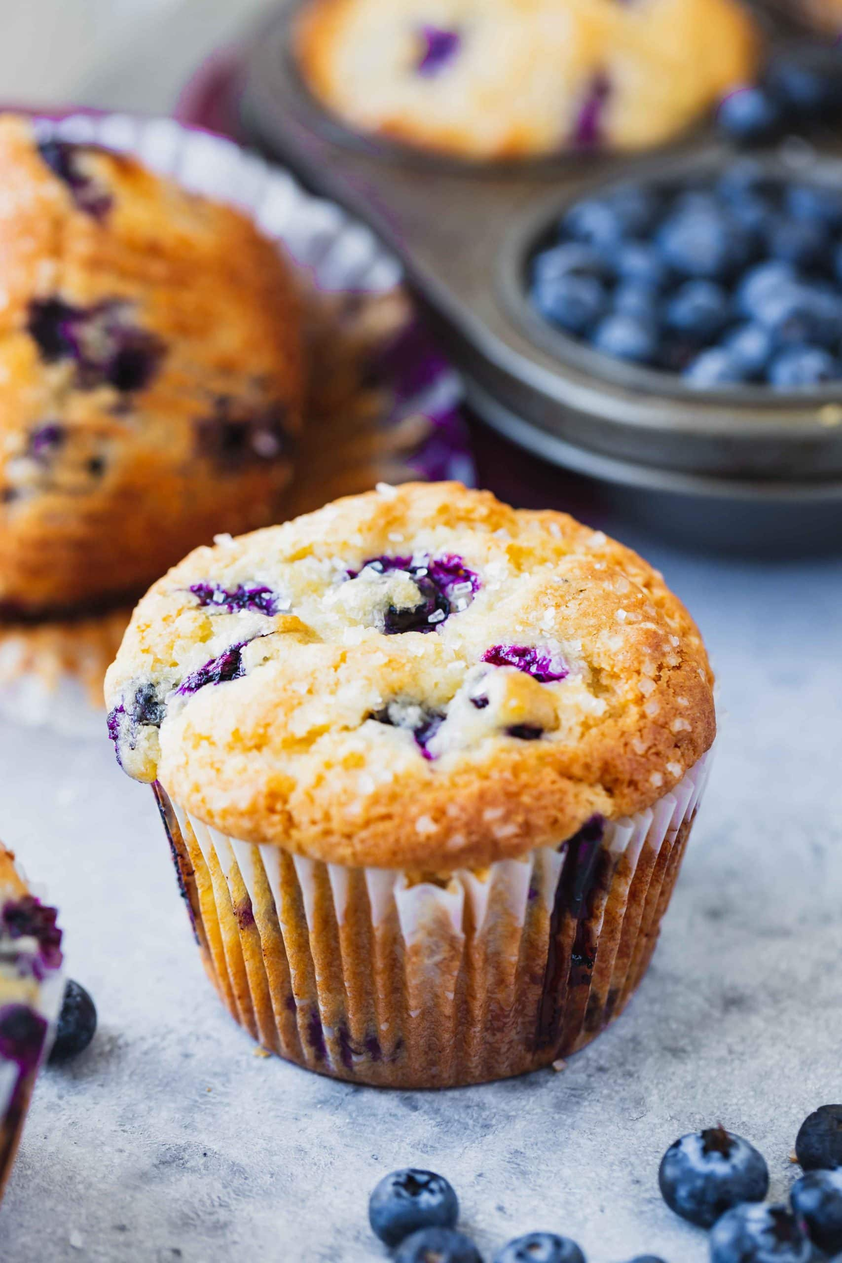 Two blueberry muffins baked to golden brown and filled with blueberries.  In the background is a frying pan filled with blueberries.