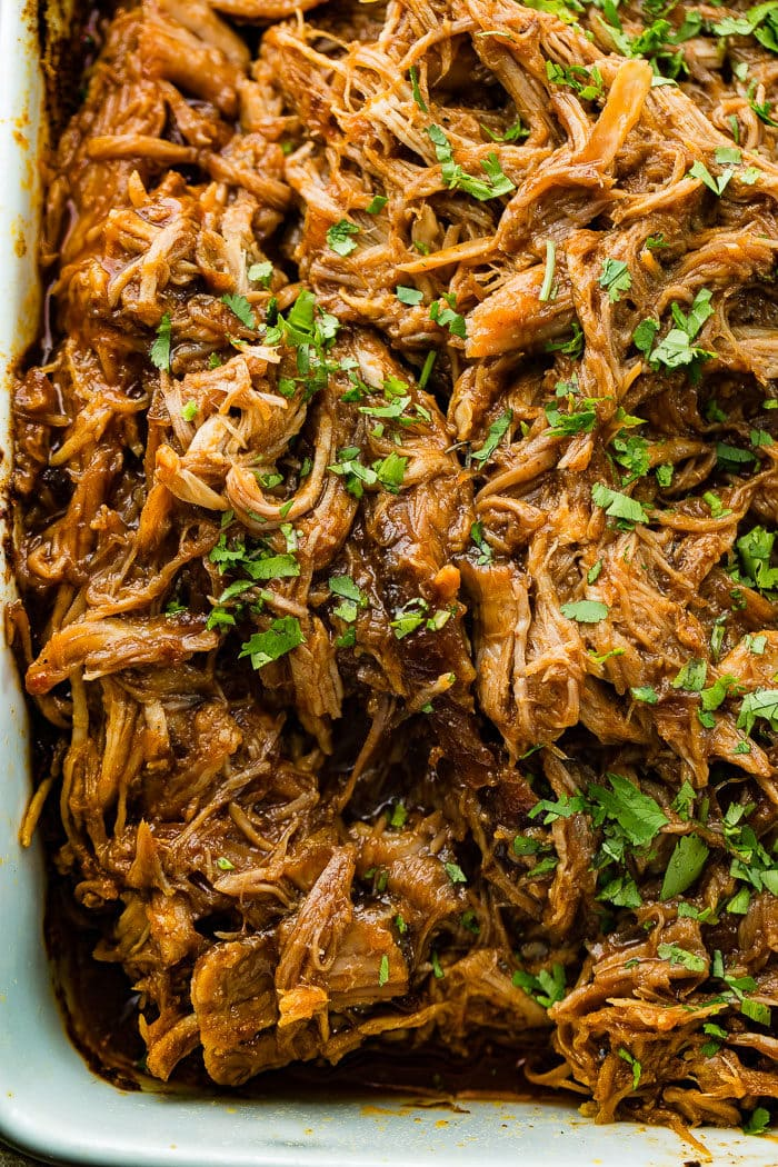 an entire pan of shredded cafe rio sweet pork copycat recipe with chopped cilantro on top