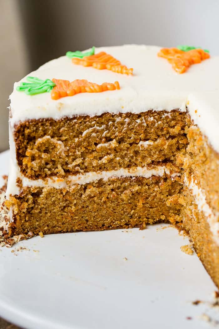 A photo of a two layer carrot cake on a white cake stand looking at the cake from the side with a slice taken out of it. It has white cream cheese frosting in between the layers and all over the outside. The cake is topped with white chocolate decorative carrots.