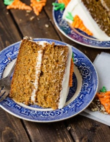A photo of a slice of two layer carrot cake laying on its side on a blue and white plate.