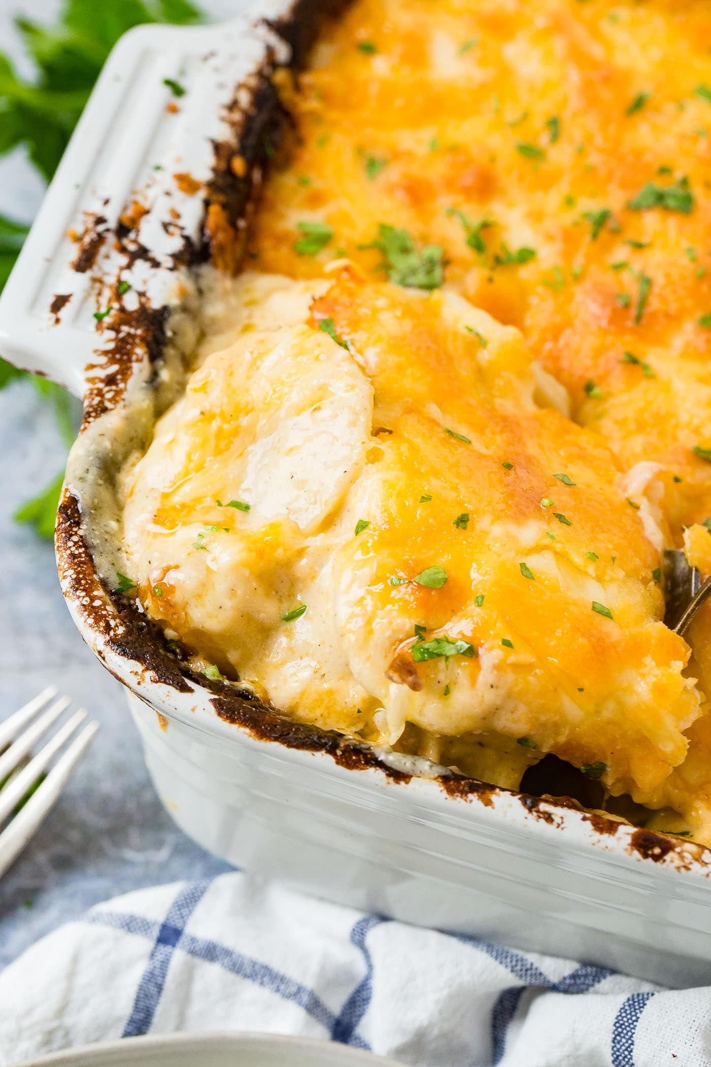 A white casserole dish loaded with cheesy potatoes casserole