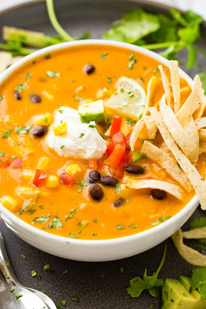 A photo of a white bowl of chicken tortilla soup topped with sour cream, a lime wedge, and tortilla strips.