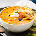 An aerial photo of a white bowl of chicken tortilla soup topped with sour cream, a lime wedge, and tortilla strips.
