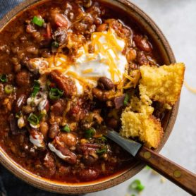 A bowl of chili. The chili has ground beef, beans and a rich sauce. It is topped with sour cream and shredded cheese and a piece of cornbread is on the edge of the bowl.