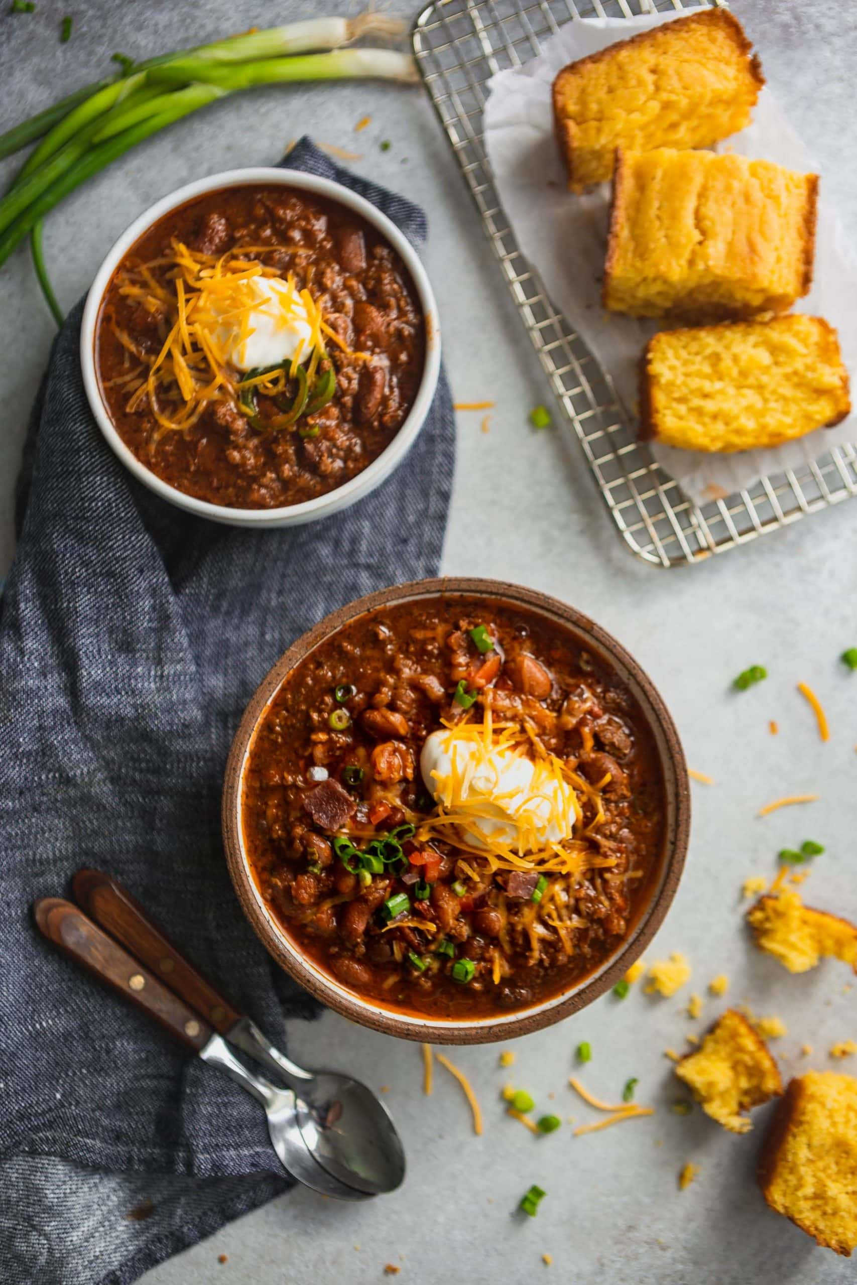 Two bowls of the best chili. The chili is made with beans, ground beef and herbs and spices. It is topped with sour cream and grated cheese.
