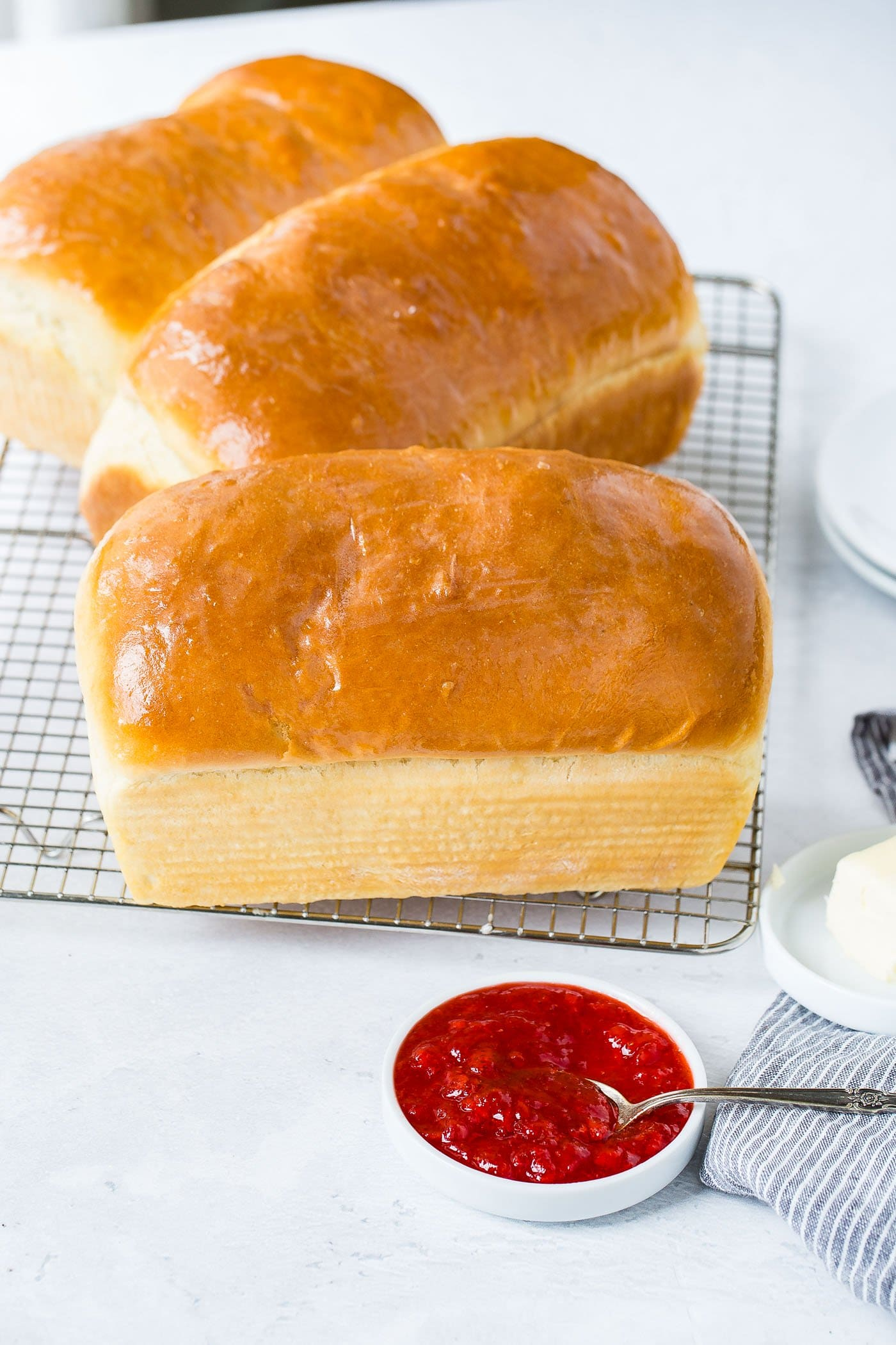 Three loaves of fresh baked, homemade white bread, sitting on a wire cooling rack. There are two bread plates, a dish of butter, and a small container of strawberry jam next to the bread.