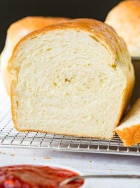 A loaf of homemade white bread that has a slice removed. It is soft, and white inside and the top is golden brown. The bread is on a wire cooking rack.