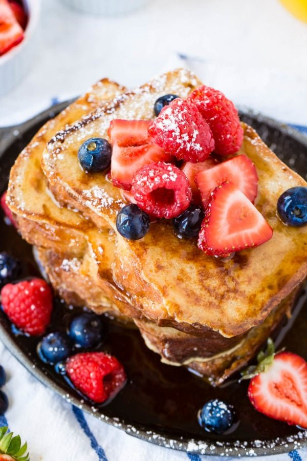 A photo of a stack of french toast covered in dripping syrup and fresh berries.