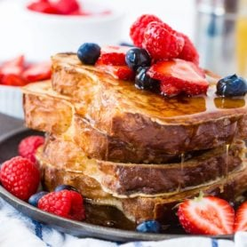A photo of how to make french toast with a stack of french toast covered in dripping syrup and fresh berries.