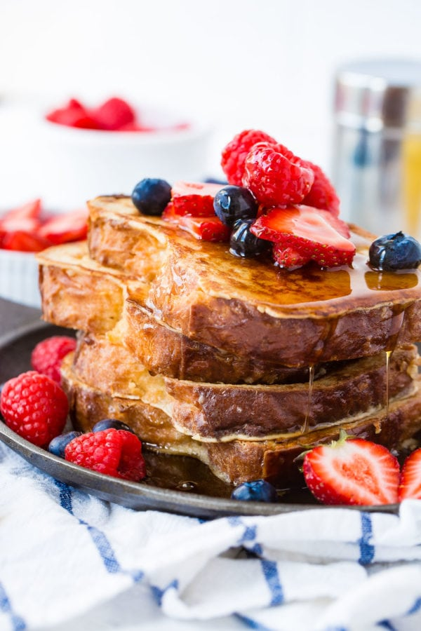 A photo of french toast with a stack of french toast covered in dripping syrup and fresh berries.