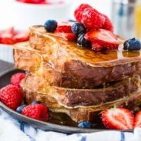 a stack of french toast with maple syrup and berries on top