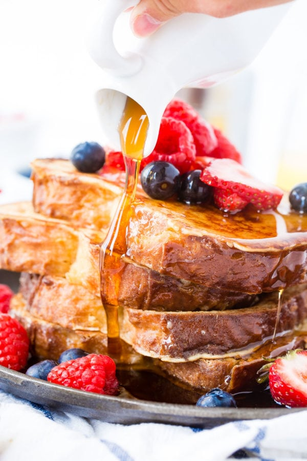 A photo of syrup being poured over a stack of french toast covered in fresh berries.