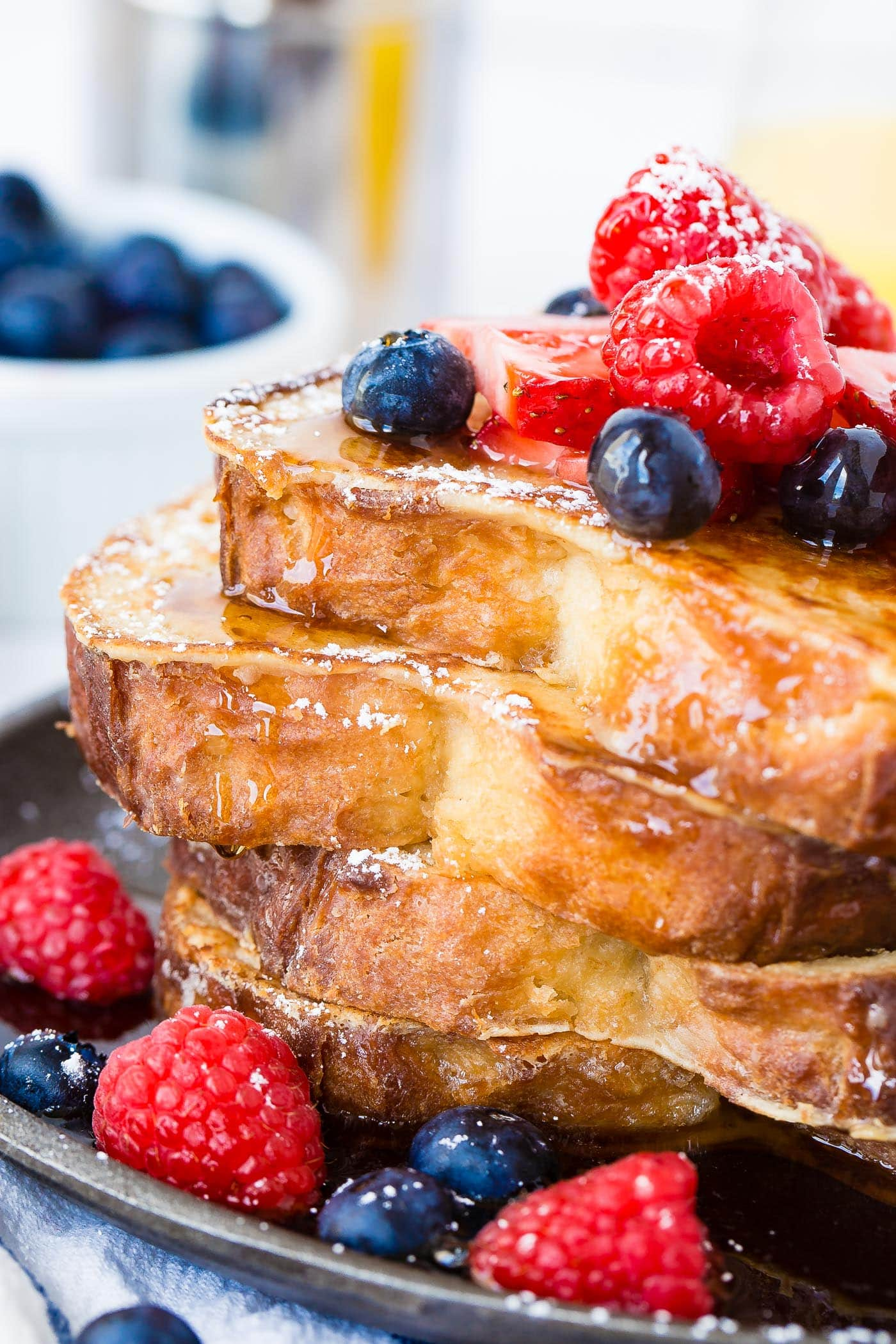 A photo of a stack of 4 perfectly made french toast slices dripping with syrup and fresh berries. How to Make French Toast
