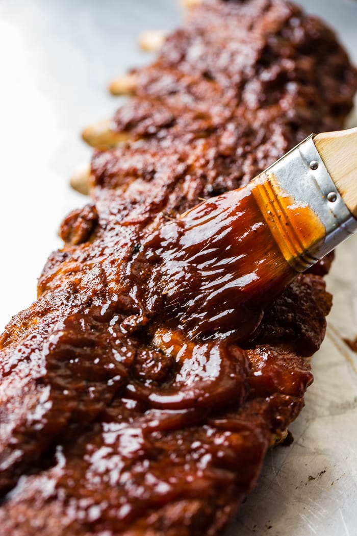 A baking sheet with a rack of ribs and a basting brush slathering on bbq sauce to make the smoky bbq instant pot ribs recipe