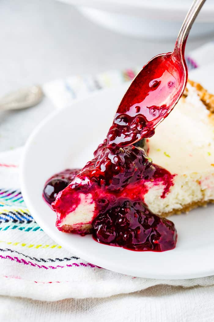 A photo of triple berry sauce being poured with a spoon onto a slice of lime cheesecake.