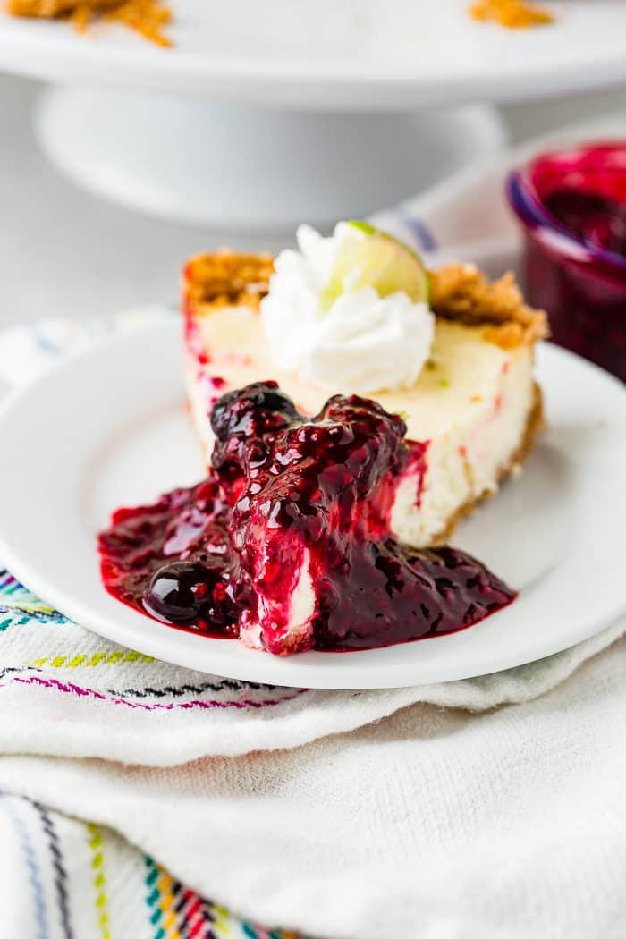A photo of a slice of lime cheesecake on a while plate covered in triple berry sauce and dollop of whipped cream and a slice of lime.