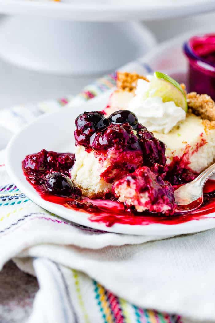 A photo of a slice of lime cheesecake with triple berry sauce on a white plate with a bite taken out of it with berry sauce dripping all around it.