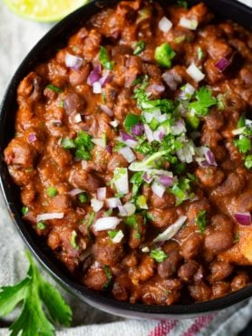 A photo of a bowl of Mexican black beans stopped with diced red onion and chopped fresh cilantro.