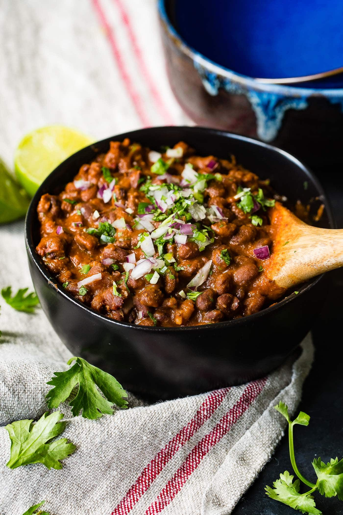 A photo of a bowl of Mexican black beans stopped with diced red onion and chopped fresh cilantro being scooped with a wooden spoon.