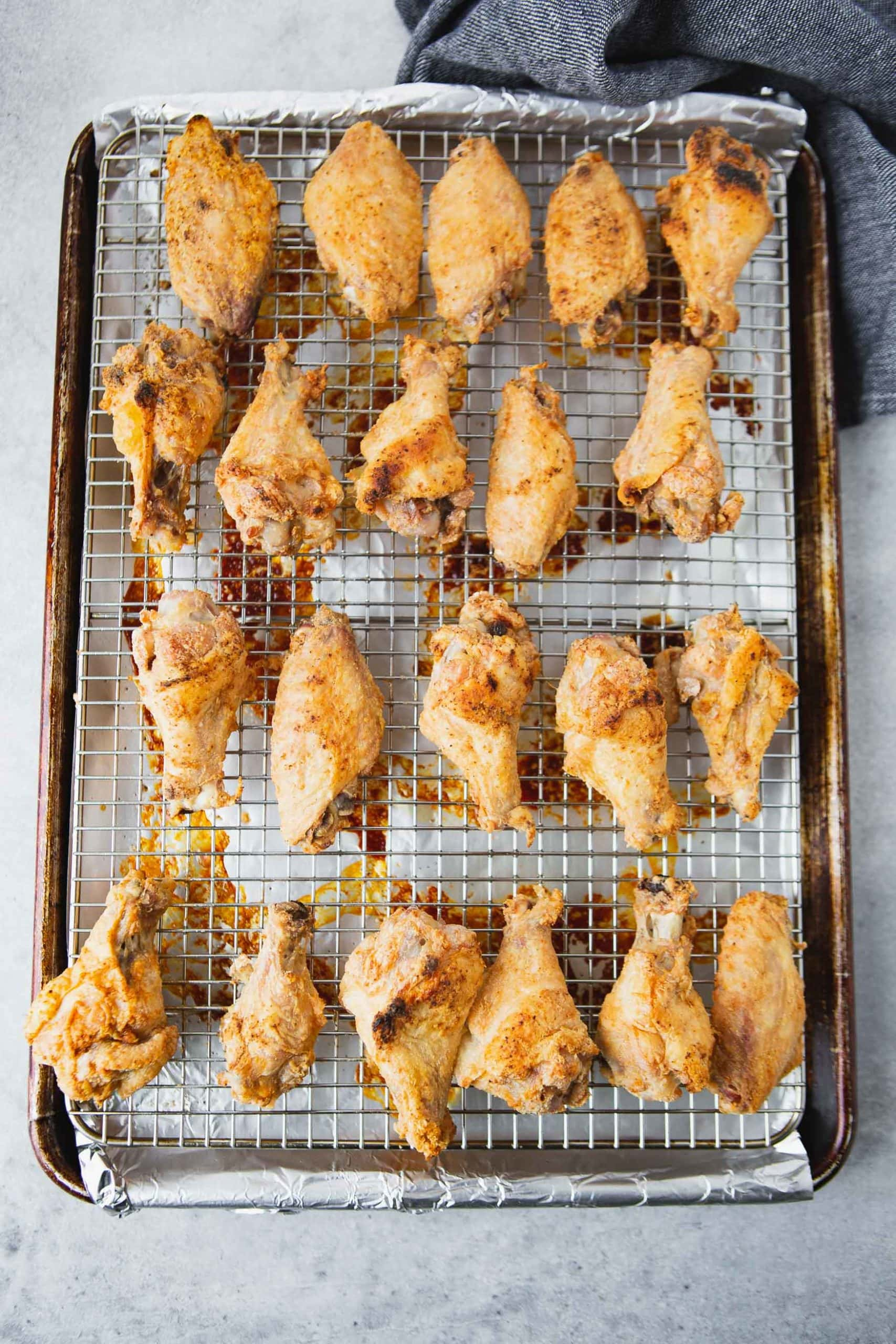 a photo of golden baked chicken wings on a wire rack in a baking sheet.