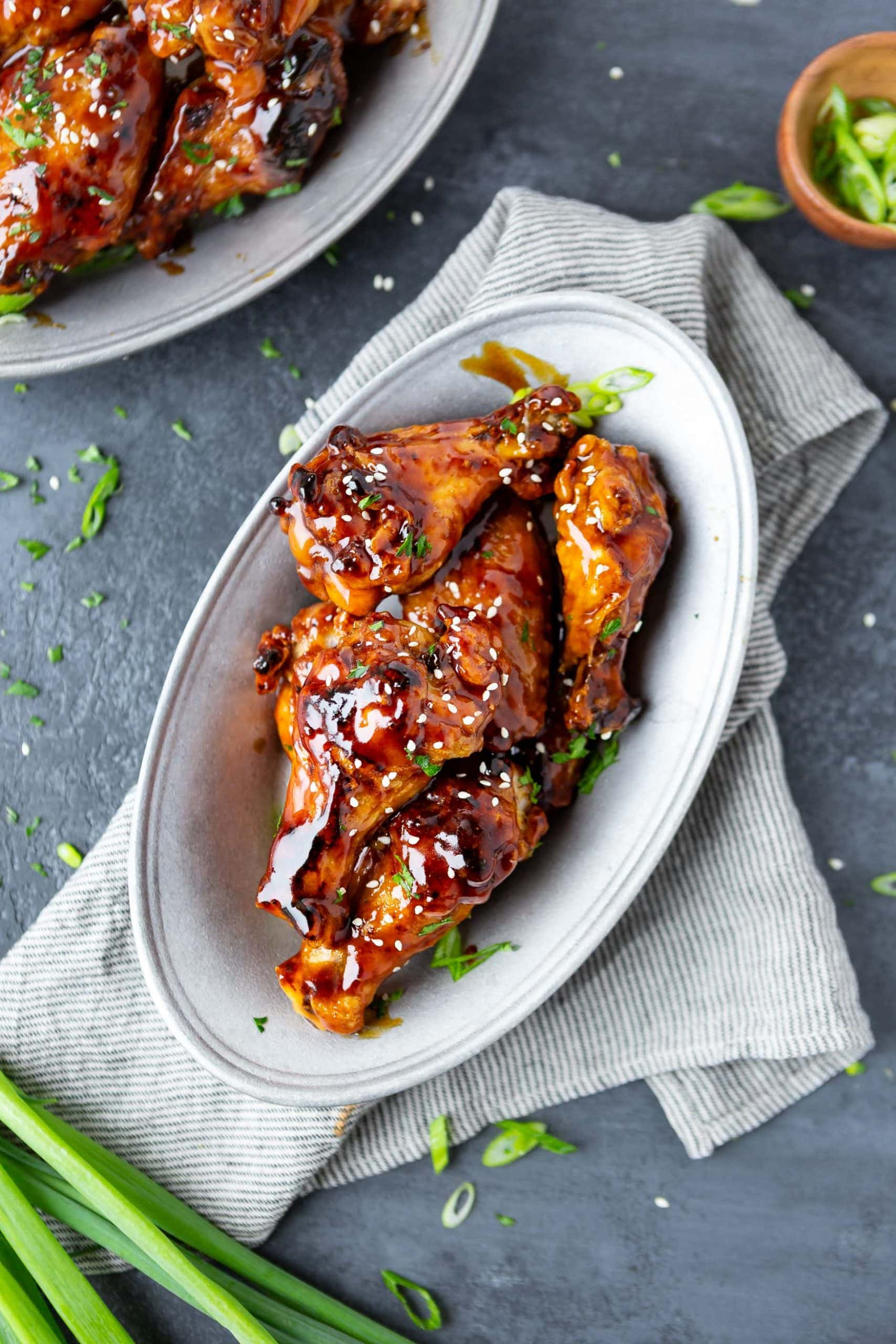 a photo taken from above of several baked chicken wings coated in teriyaki sauce and topped with sprinkled sesame seeds on a large white platter