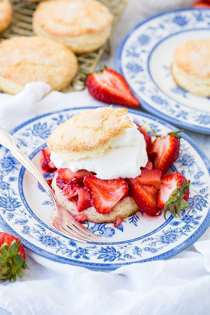 A photo of homemade strawberry shortcake recipe on a blue and white plate with a sweet biscuit, juicy strawberries, and whipped cream.