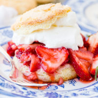 A closeup photo of homemade strawberry shortcake recipe on a blue and white plate with a sweet biscuit, juicy strawberries, and whipped cream.