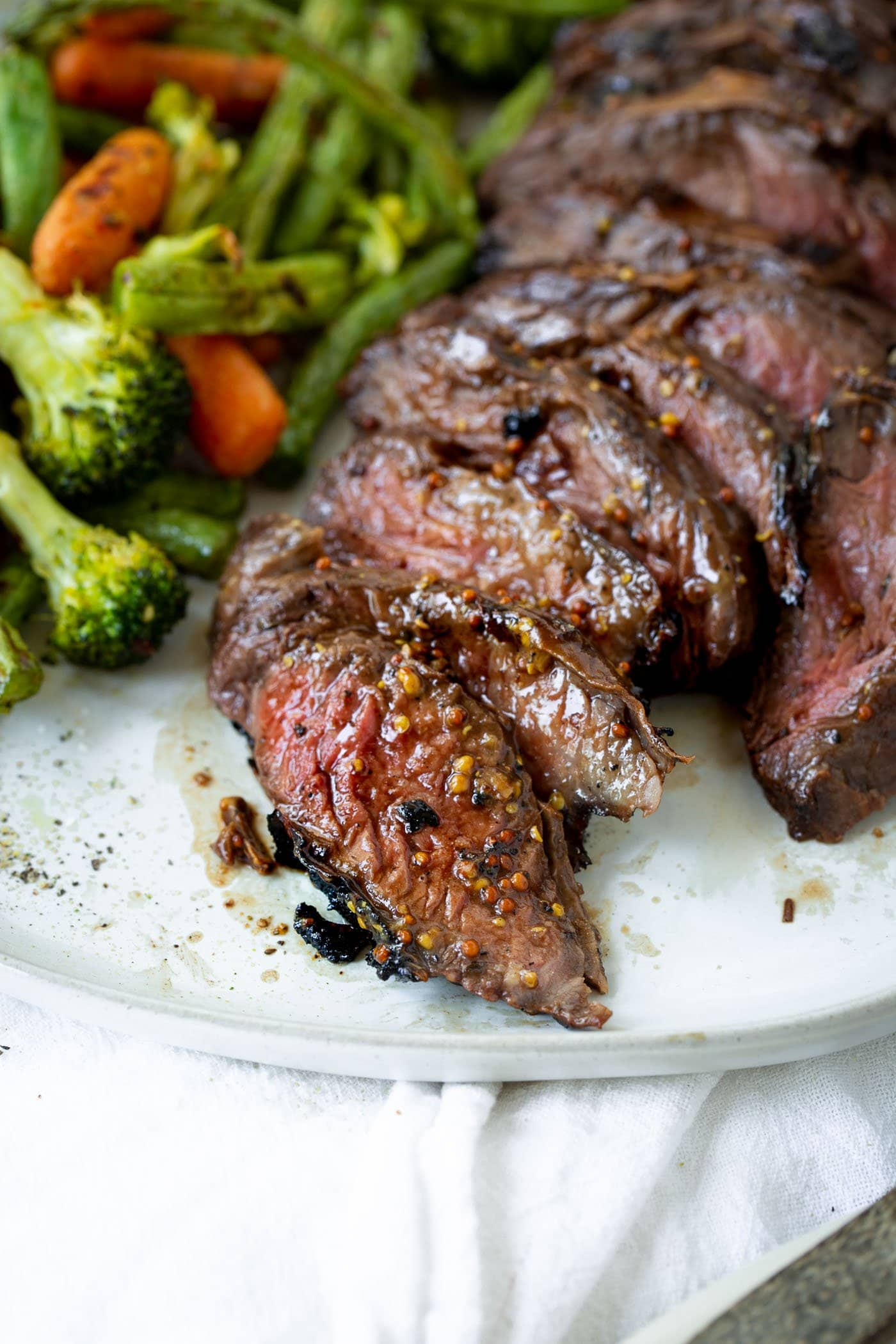 A close up photo of sliced medium rare hanger steak on a white plate next to some roasted vegetables.
