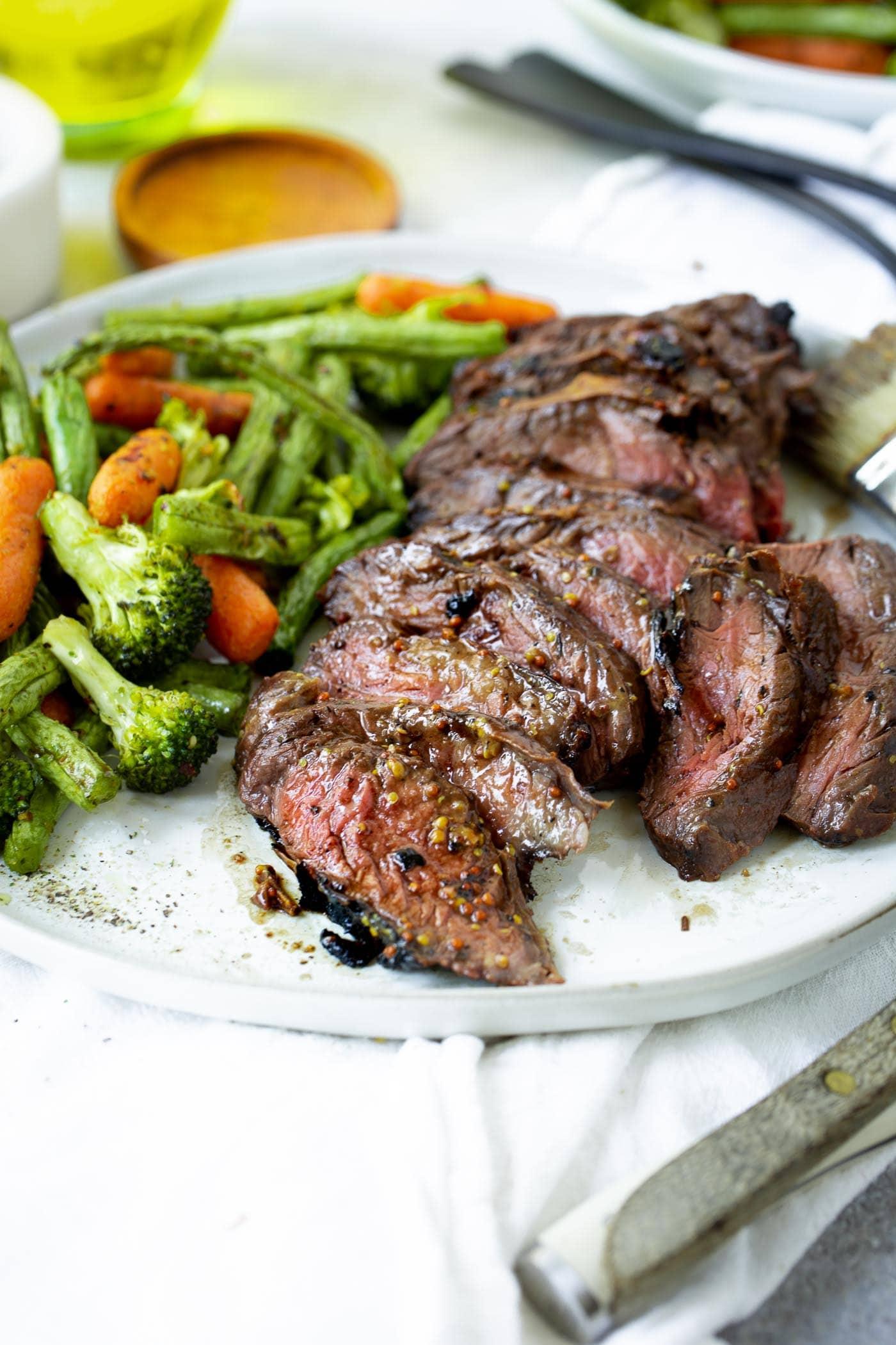 A photo of sliced medium rare hanger steak on a white plate alongside roasted vegetables.