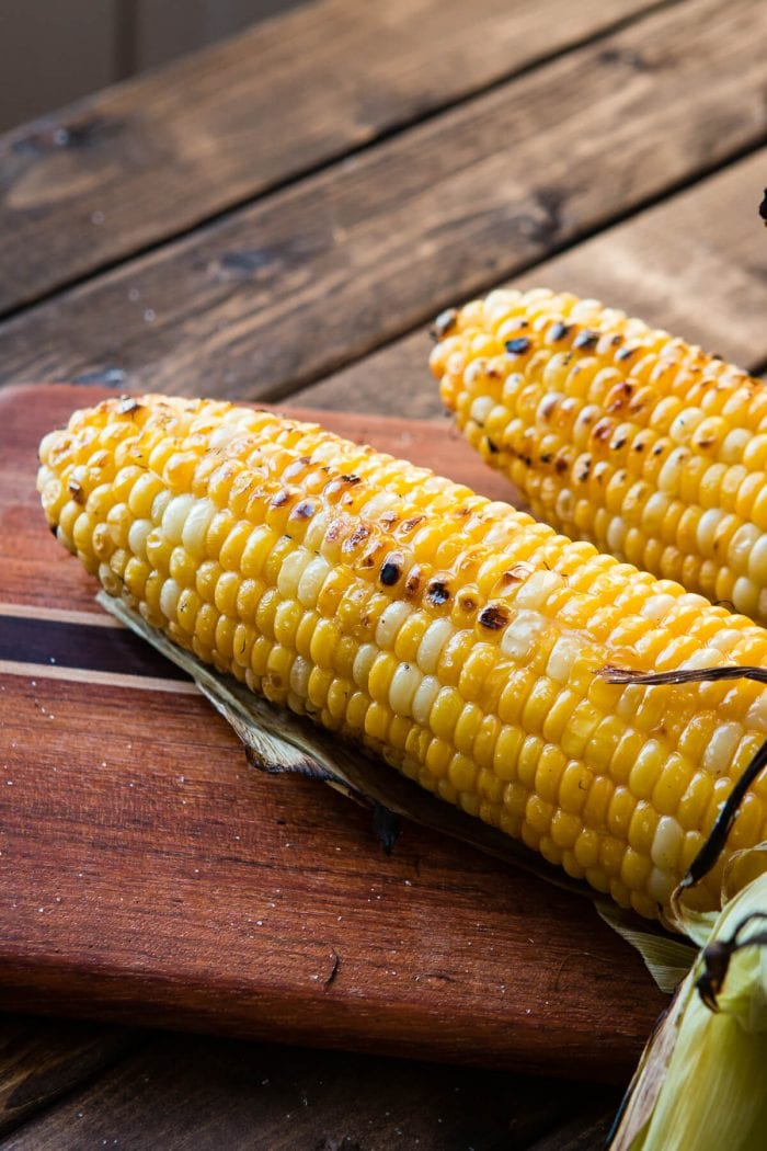 two ears of grilled corn on cutting board