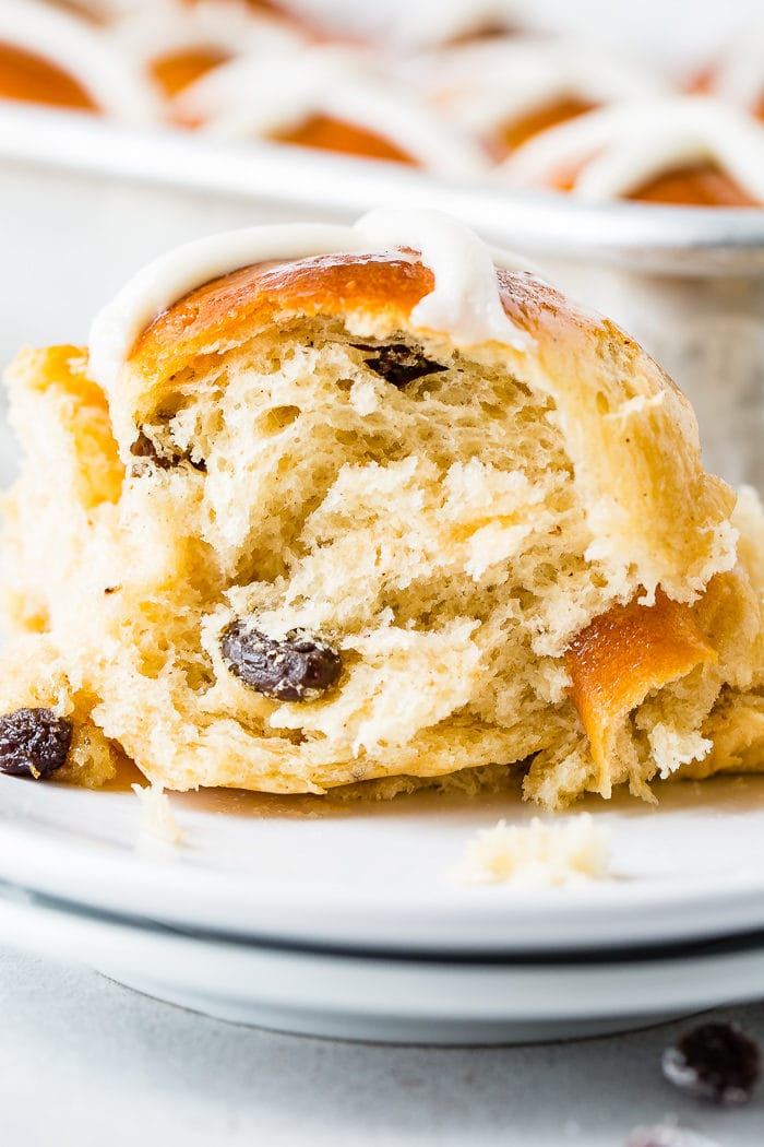 A photo of a cross section of a hot cross bun sitting on a white plate full of raisins and topped with a white frosting cross.